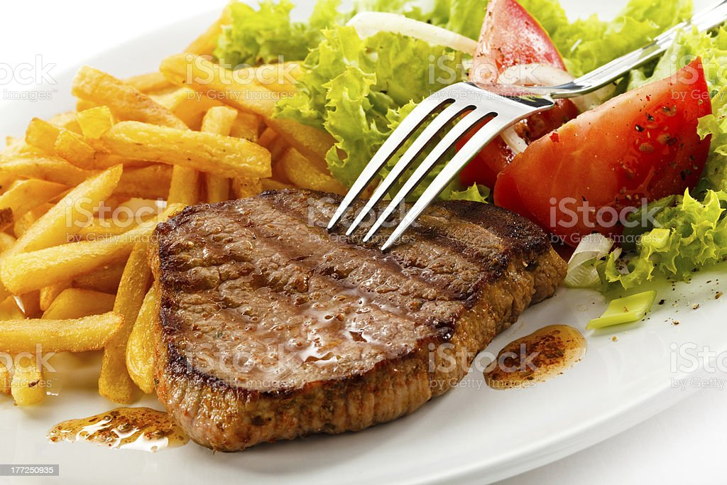 Plate of grilled meat and vegetables with French fries stock photo
