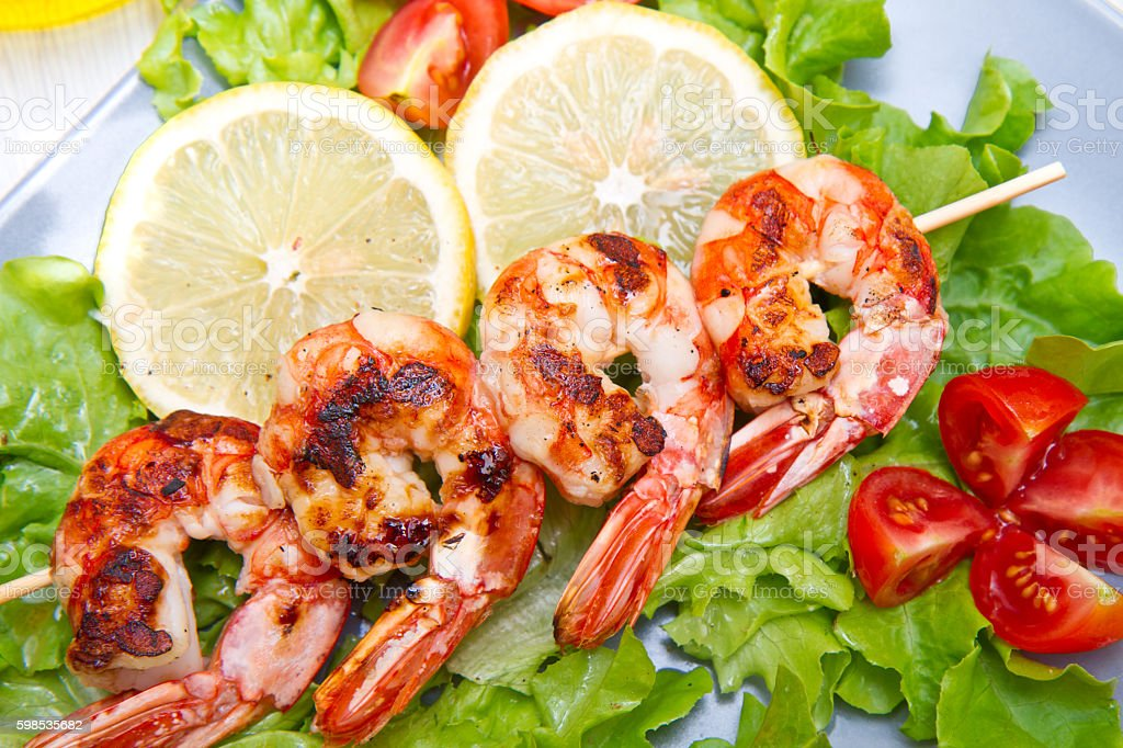 plate of grilled prawns with salad and cherry tomatoes photo libre de droits
