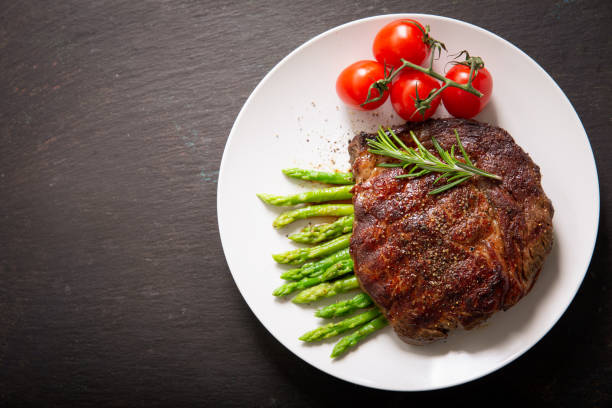 plate of grilled steak with rosemary and asparagus, top view stock photo