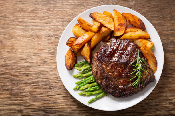 plate of grilled steak with rosemary, asparagus and potato, top view stock photo