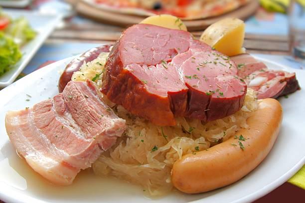 assiette de jambon, saucisse, accompagnées d'une choucroute - choucroute alsacienne photos et images de collection