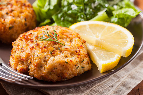 plate of homemade organic crab cakes with veg and lemon - bumpy stock pictures, royalty-free photos & images