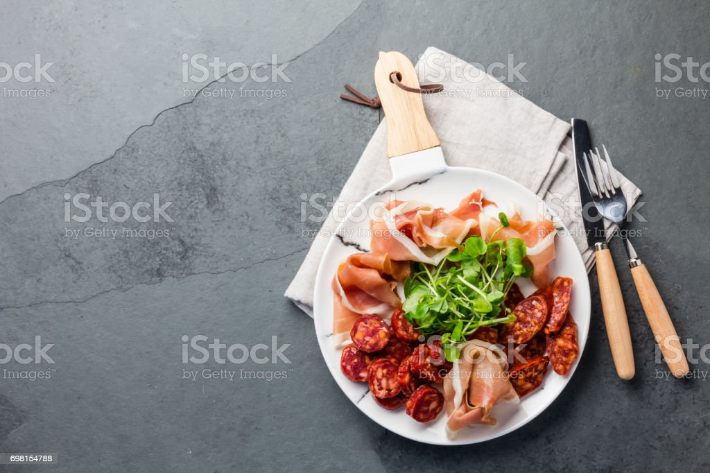 Plate of iberian spanish antipasto - ham serrano and salami stock photo