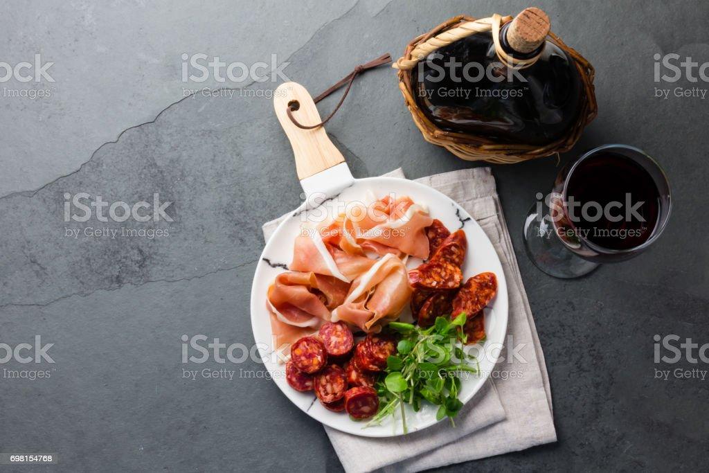 Plate of iberian spanish antipasto - ham serrano and salami with red wine stock photo
