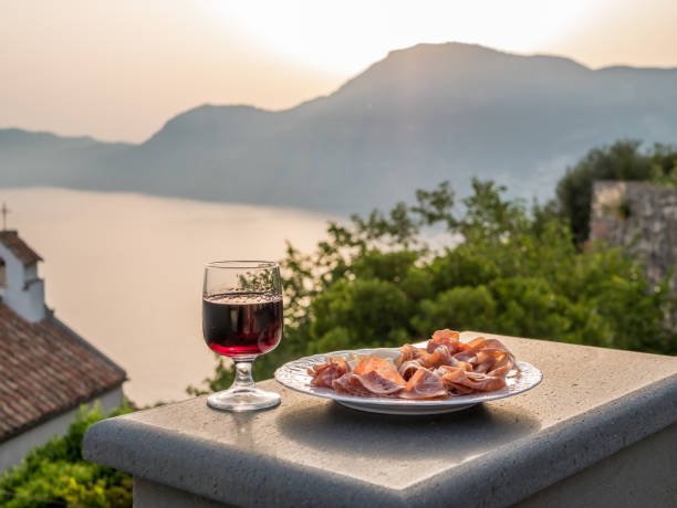 Plate of italian food with cured meat, salami and parmesan cheese and a glass of red wine. Amalfi coast in background. stock photo