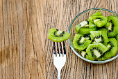 A plate of kiwi fruit slices with fork on wooden table.