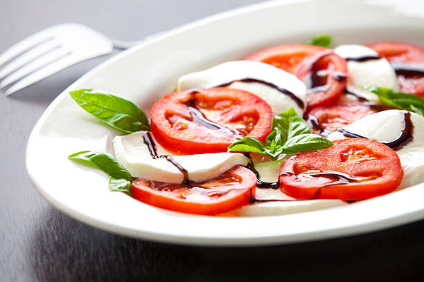 Plate of Layered Tomato And Mozzarella with Balsamic Glaze Closeup stock photo