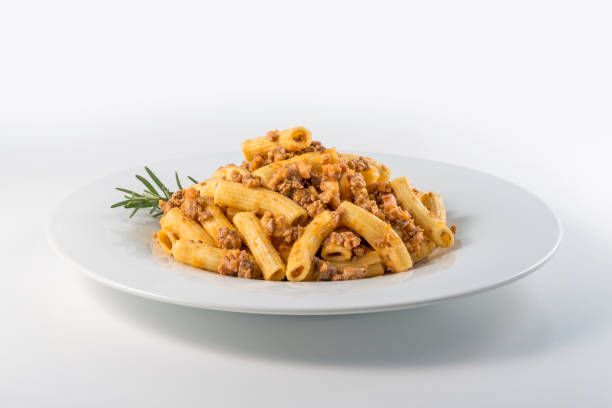 Plate of macaroni pasta with Bolognese ragù Round white Plate of macaroni pasta with Bolognese ragù rigatoni stock pictures, royalty-free photos & images