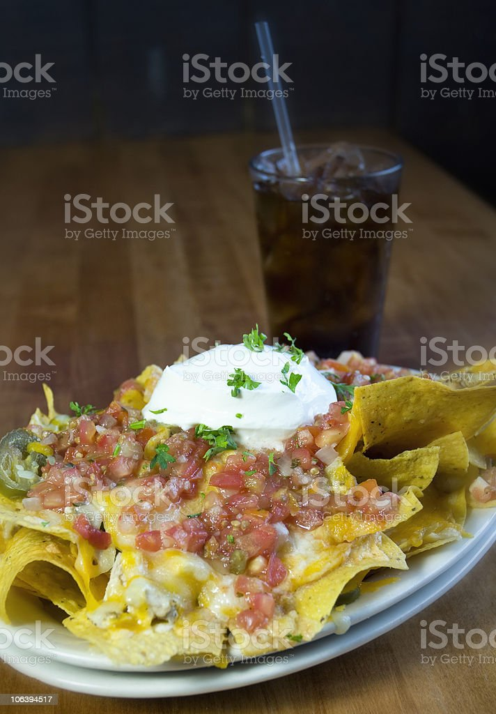 Plate Of Nachos With Soft Drink On A Restaurant Table royalty-free stock photo