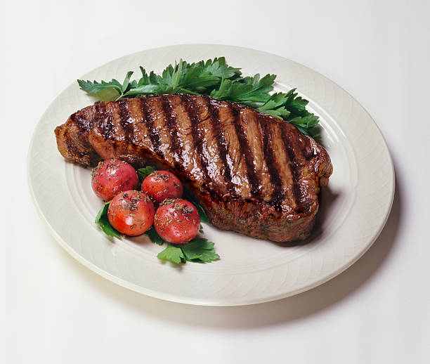 plate of new york strip steaks with tomatoes on side - strip steak stockfoto's en -beelden
