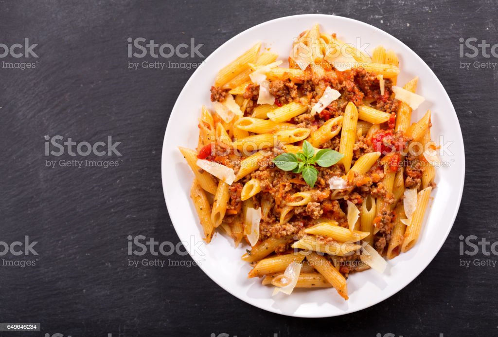 plate of pasta bolognese on dark table stock photo