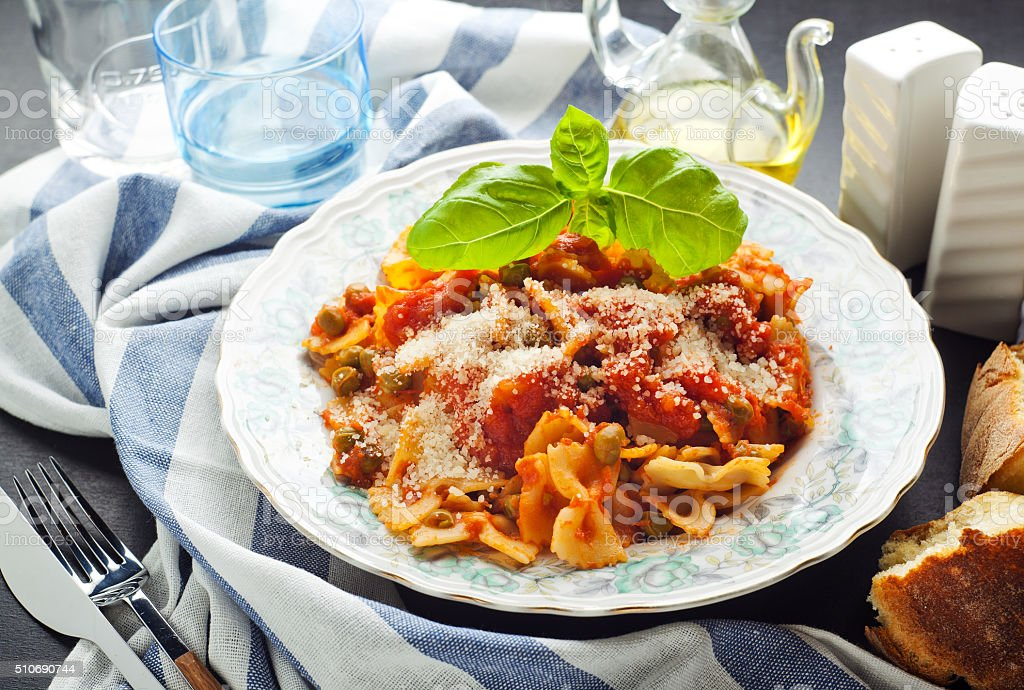 plate of pasta farfalle with tomato sauce and green peas. stock photo