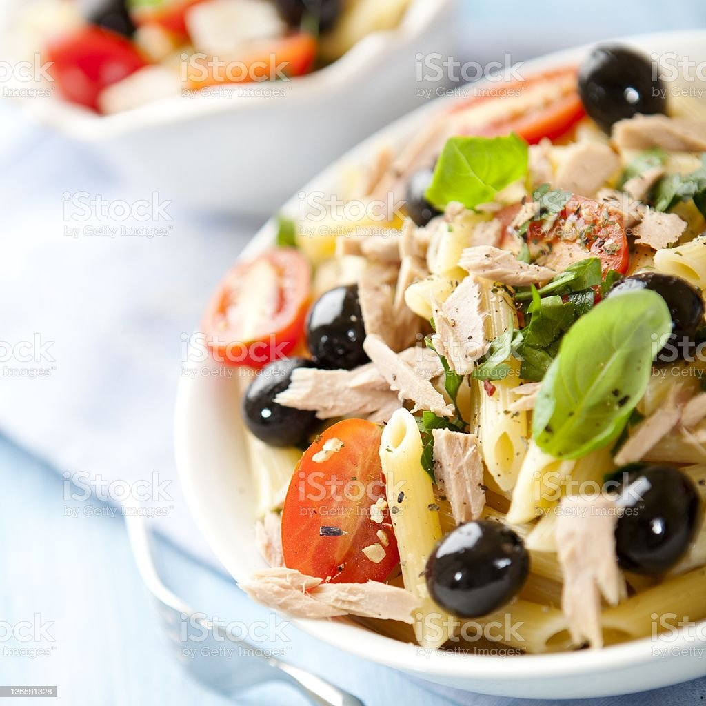 Plate of pasta salad with tuna, olives, tomato and spinach stock photo