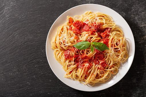 plate of pasta with tomato sauce on dark table, top view