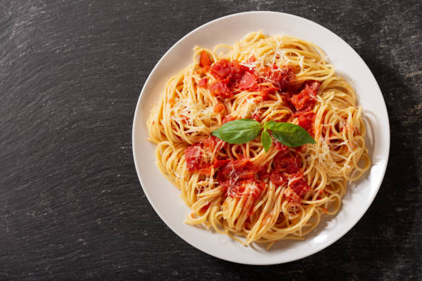 plate of pasta with tomato sauce, top view plate of pasta with tomato sauce on dark table, top view spaghetti stock pictures, royalty-free photos & images