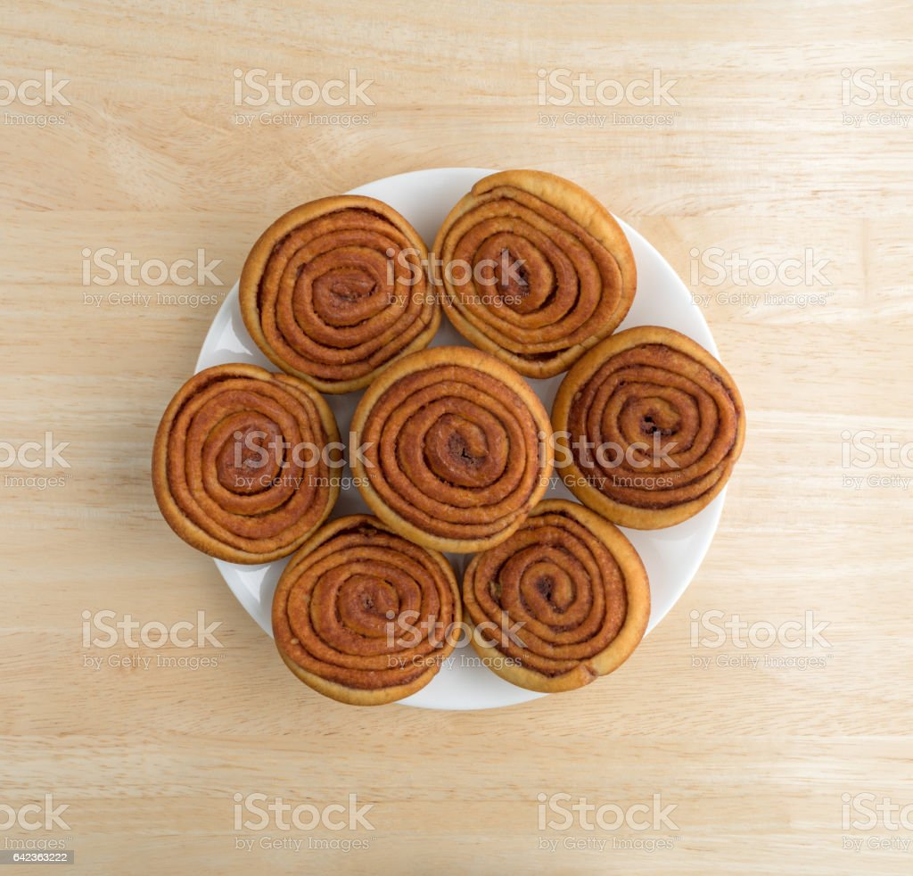 Plate of pecan sweet rolls on a wood table stock photo