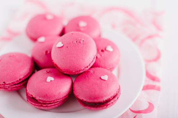 ピンクのマカロンと砂糖心装飾のプレート。白い木製の背景。 ストックフォト
