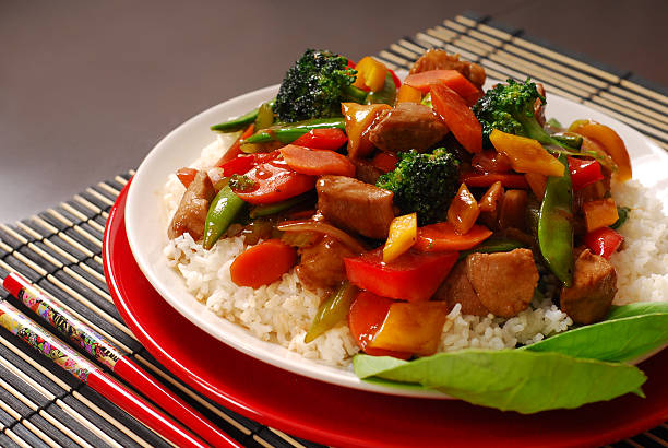 plate of pork stir fry with vegetables - chinese food stock photos and pictures