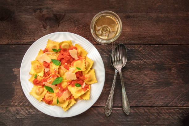 teller mit ravioli mit tomaten-sauce und weißwein - weinsoße stock-fotos und bilder
