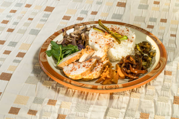 Plate of rice and chicken breast with mushrooms and vegetables stock photo