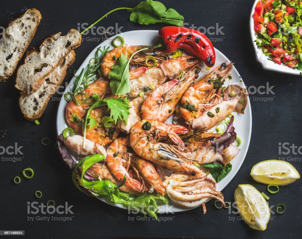 Plate of roasted tiger prawns and octopus pieces with fresh leek, salad, peppers, lemon, bread, pesto sauce over black background stock photo