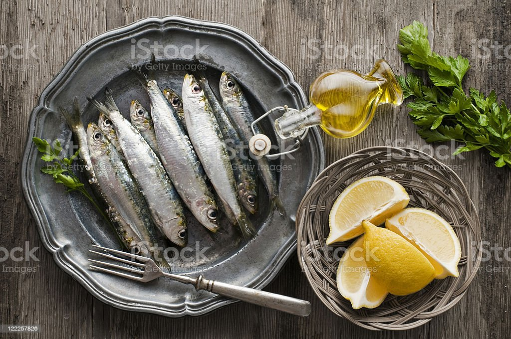 Plate of sardines with lemon and olive oil on a wooden table stock photo