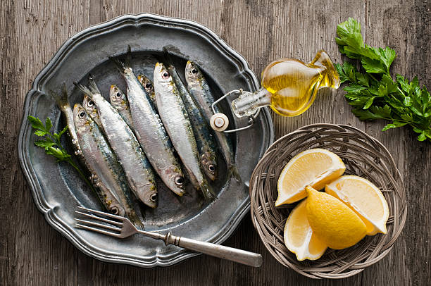 Plate of sardines with lemon and olive oil on a wooden table Fresh raw sardines with parsley and lemon on wooden background anchovy stock pictures, royalty-free photos & images