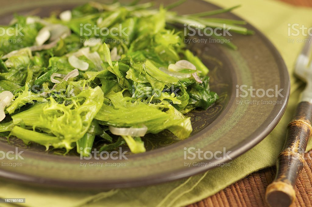 Plate of Sauteed Leafy Greens with Shallots royalty-free stock photo