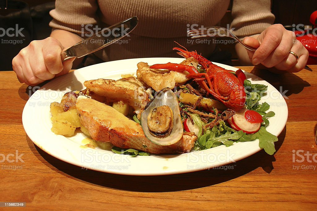 Plate of seafood and salad with knife and fork poised above royalty-free stock photo