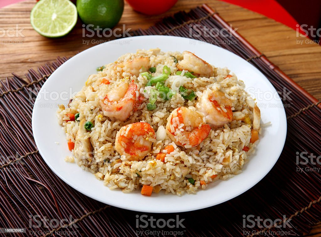 Plate of shrimp fried rice on a placemat and wood table stock photo