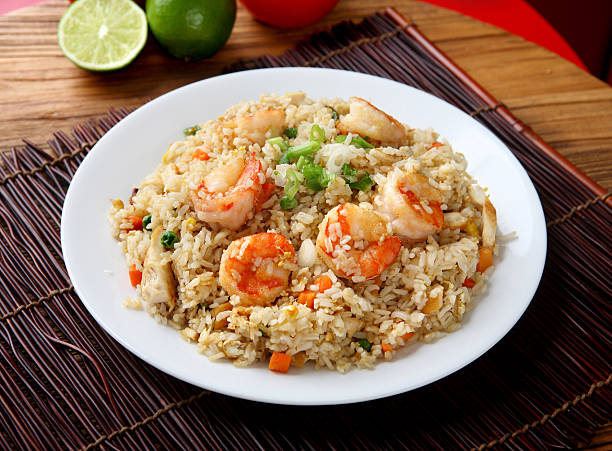 Plate of shrimp fried rice on a placemat and wood table Shrimp & Chicken Fried Rice fried rice stock pictures, royalty-free photos & images