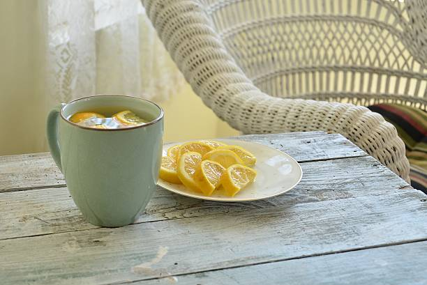 Plate of Sliced Lemons and Mug of Lemon Water stock photo
