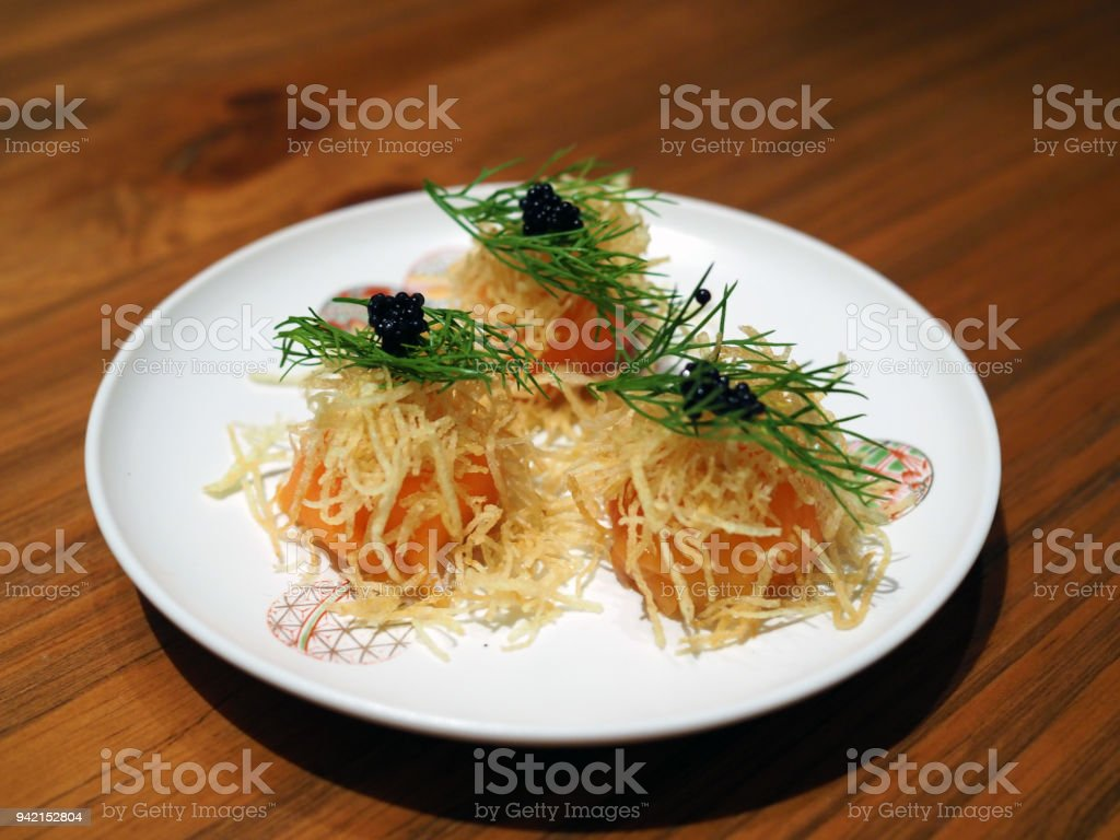 Plate of Smoked salmon roll stuffed with cream cheese topped with fried potato and caviar. stock photo