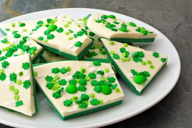 plate of st patricks day candy bark with shamrock sprinkles - st patricks day food stock photos and pictures