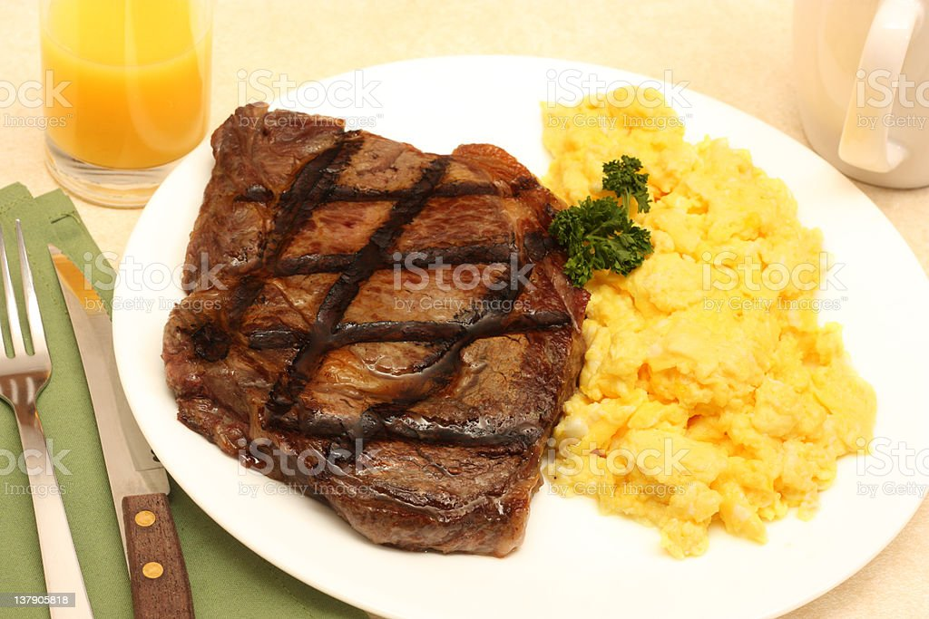 A plate of steak and scrambled eggs stock photo