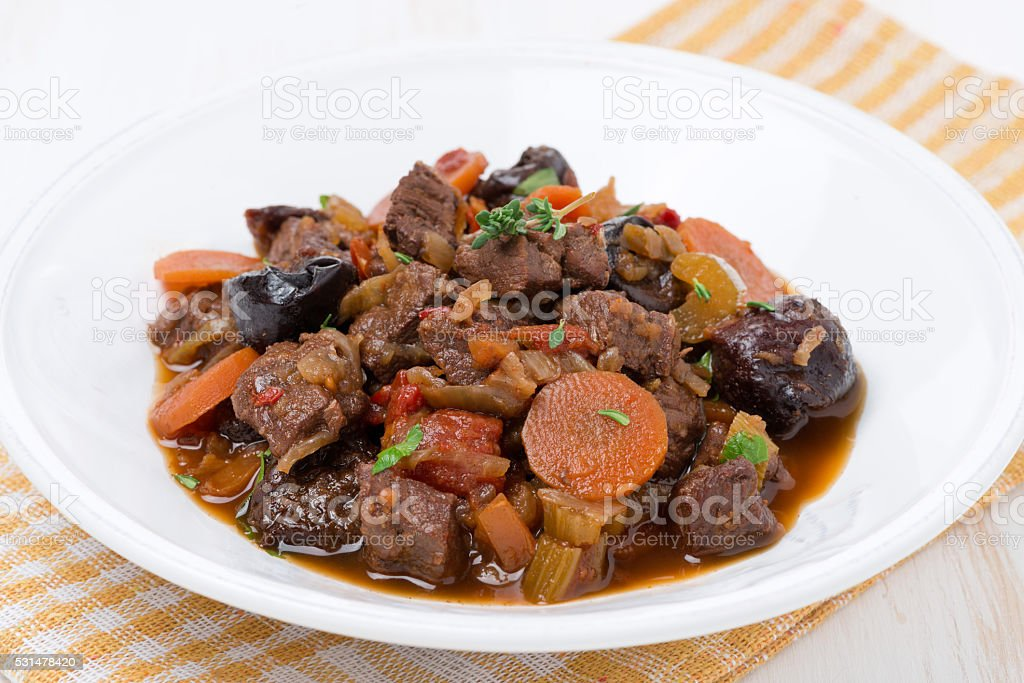 plate of stew with beef and vegetables stock photo