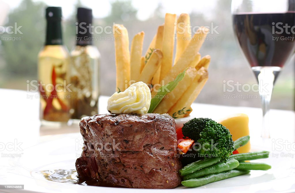 Plate of tenderloin steak, fries and vegetables royalty-free stock photo