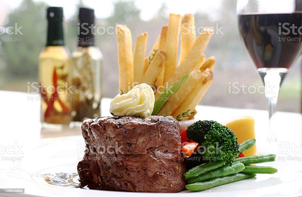 Plate of tenderloin steak, fries and vegetables stock photo
