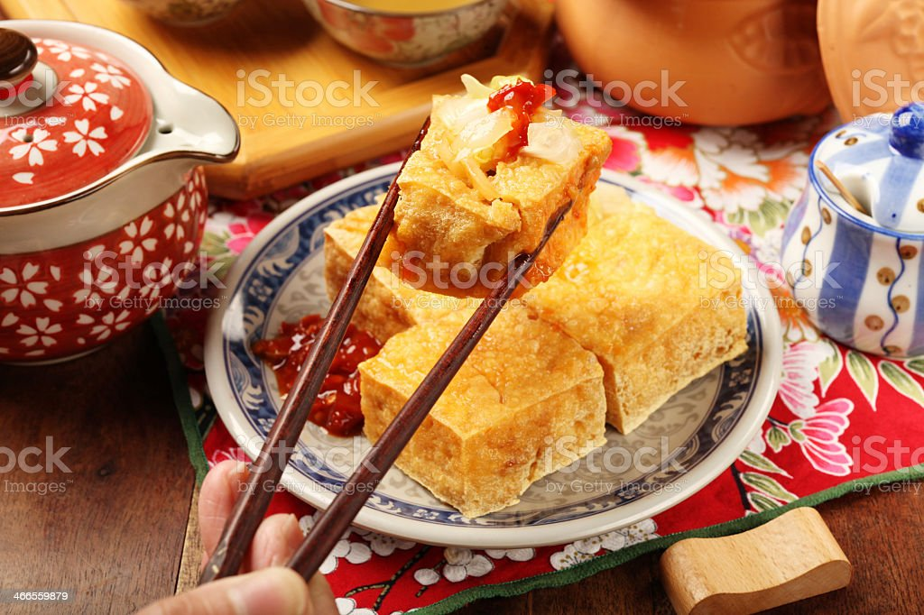 Plate of tofu being picked up with chopsticks stock photo