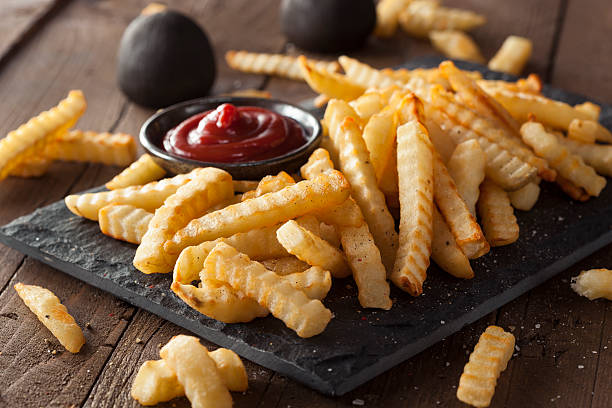 a plate of unhealthy baked crinkle french fries and ketchup - friet stockfoto's en -beelden