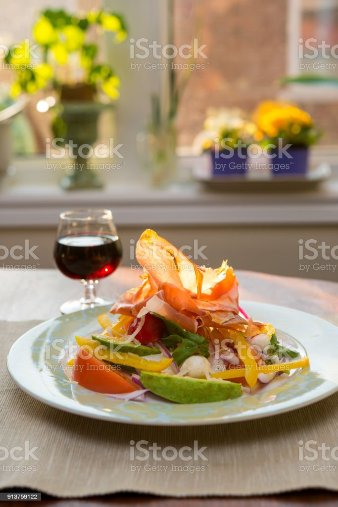 Plate of vegetable, bocconcini and prociutto salad in evening sunlight stock photo