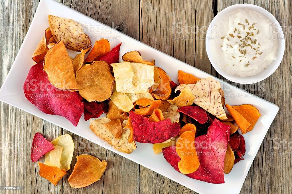 Plate of vegetable chips with dip from above on wood stock photo