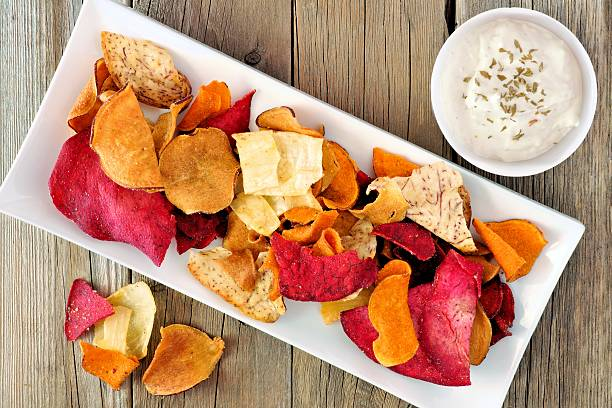plate of vegetable chips with dip from above on wood - gemüsechips stock-fotos und bilder