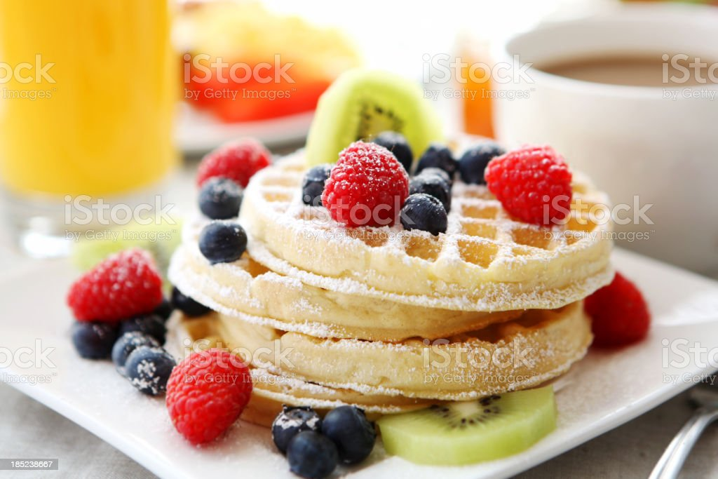 A plate of waffles topped with berries, sugar and kiwi  stock photo