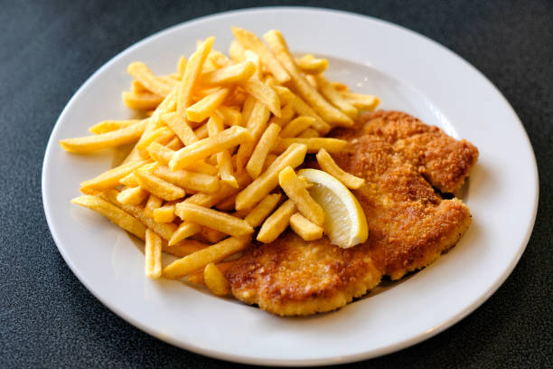 plate of wiener schnitzel with fried potatoes - escalope imagens e fotografias de stock