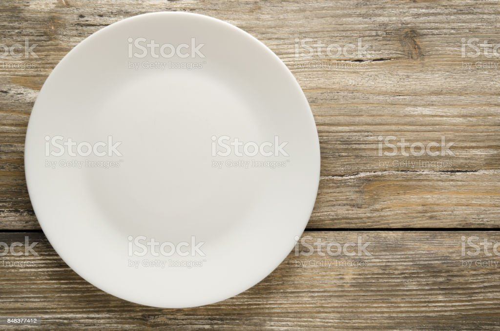 plate on a wooden background. plate top view. copy space stock photo