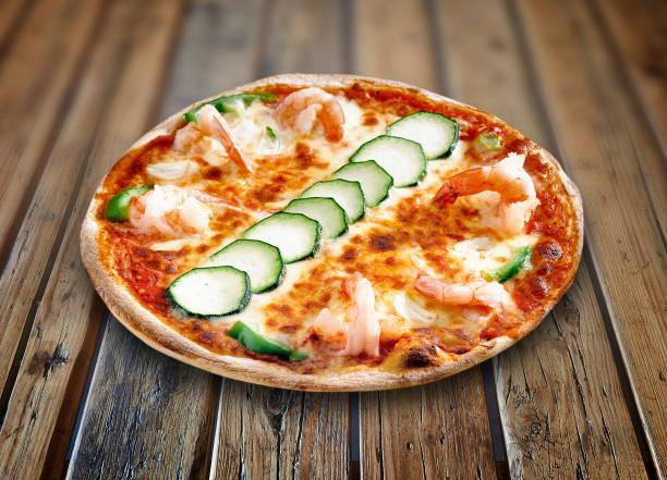 Teller auf Holztisch mit einer leckeren Pizza – Foto