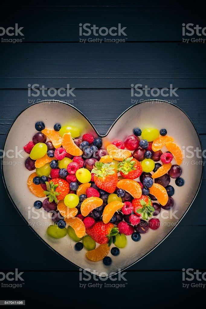 Plate shape heart full colorful fruits stock photo
