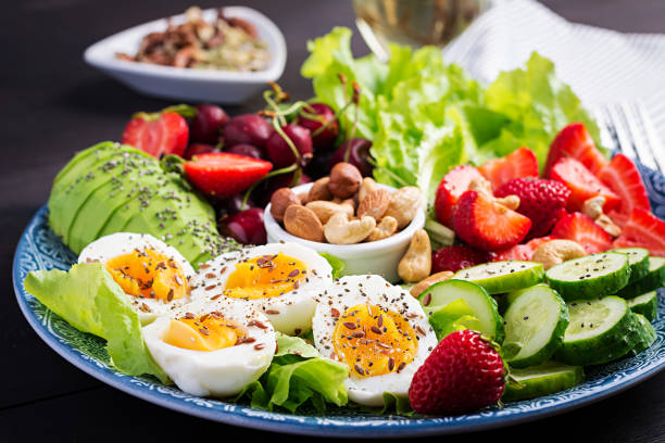 Plate with a paleo diet food. Boiled eggs, avocado, cucumber, nuts, cherry and strawberries. Paleo breakfast. stock photo