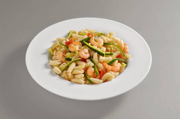 platte mit einer portion sardische gnocchi mit garnelen und zucchini - safransauce stock-fotos und bilder